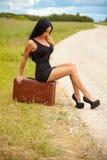 La señora joven está esperando cualquier coche en el camino Fotografía de archivo