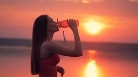 La señora joven está lanzando su pelo largo y está bebiendo de una botella metrajes