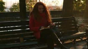 La señora joven está leyendo un libro, cabeza roja que la muchacha preciosa se está sentando en banco de parque, escena colorida  metrajes