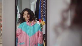 La señora joven está mirando el espejo, aplicando a sí misma dos chaquetas en tienda almacen de video