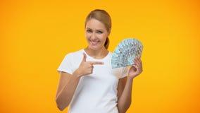 La señora joven feliz que señala en los billetes de banco del dólar da, renta pasiva, inversión almacen de video