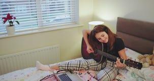 La señora joven grande sonriente feliz disfrutando del tiempo en su dormitorio que juega en una guitarra después de escuela tiene almacen de video