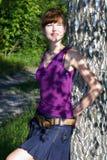 La señora joven hermosa en blusa púrpura y el dril de algodón bordean la presentación al aire libre imágenes de archivo libres de regalías