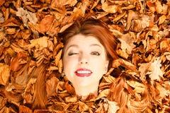 La señora joven hermosa está mintiendo entre las hojas Imágenes de archivo libres de regalías