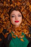 La señora joven hermosa está mintiendo entre las hojas Fotos de archivo