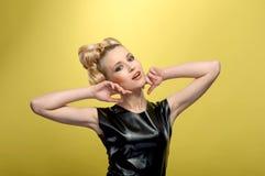 La señora joven hermosa que lleva a cabo las manos acerca a la cara Imagen de archivo libre de regalías