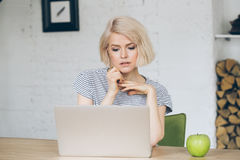 La señora joven hermosa se sienta delante de un ordenador portátil Apple al lado de ella Imágenes de archivo libres de regalías
