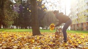 La señora joven juega con su perro próximo su buiding en ciudad metrajes