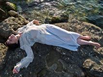 La señora joven los éticas viste la mentira en roca del mar Fotos de archivo libres de regalías