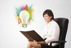 La señora joven que dibuja una bombilla colorida con colorido salpica Imagenes de archivo