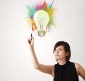 La señora joven que dibuja una bombilla colorida con colorido salpica Foto de archivo libre de regalías