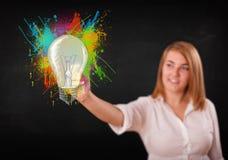 La señora joven que dibuja una bombilla colorida con colorido salpica Imagen de archivo