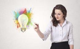 La señora joven que dibuja una bombilla colorida con colorido salpica Fotografía de archivo