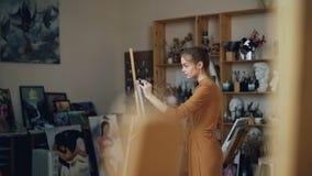 La señora joven se centra en la pintura que trabaja en estudio moderno que disfruta de la afición creativa Ilustraciones auténtic metrajes