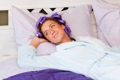 La señora joven se está reclinando sobre la cama Fotografía de archivo
