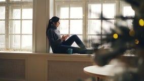La señora joven sonriente está mandando un SMS a amigos el día de la Navidad usando el smartphone que se sienta en el ventana-tra almacen de video