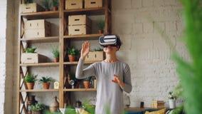 La señora joven sorprendente está disfrutando de nueva experiencia en los vidrios aumentados de la realidad que se colocan en las almacen de video