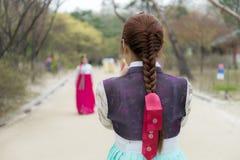 La señora joven trenzó el pelo en el traje coreano tradicional del hanbok que tomaba un handphone tirado en el parque Imagen de archivo