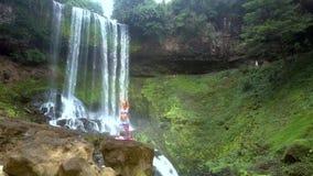 La señora lleva a cabo actitud de la yoga con las manos sobre la cabeza al lado de la cascada metrajes