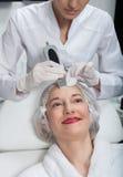 La señora madura alegre está recibiendo el tratamiento del cavitaion fotos de archivo