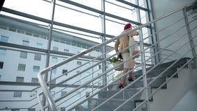 La señora mayor camina lentamente encima de las escaleras