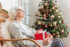 La señora mayor elegante se está sentando con su presente Foto de archivo
