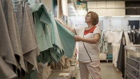 La señora mayor es de sensación y de comprobación de la toalla en una tienda, en una zona comercial almacen de metraje de vídeo