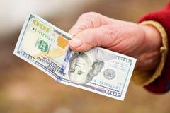 La señora mayor está sosteniendo el dinero en su mano Dinero en la mano de la mujer mayor Imágenes de archivo libres de regalías