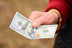 La señora mayor está sosteniendo el dinero en su mano Dinero en la mano de la mujer mayor Fotografía de archivo libre de regalías