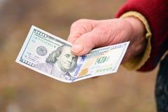 La señora mayor está sosteniendo el dinero en su mano Dinero en la mano de la mujer mayor Imagen de archivo