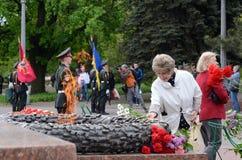 La señora mayor puso las flores a la llama eterna en conmemoración de los soldados soviéticos que lucharon contra la invasión naz Imagen de archivo