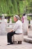 La señora mayor toma un cierto resto cerca del lago Houhai, Pekín, China Foto de archivo