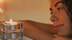 La señora mira la vela en el baño almacen de video