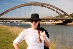 La señora morena está presentando delante del puente del arco de ALfred del puerto Imagen de archivo libre de regalías