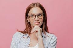 La señora pensativa del negocio sostiene la barbilla, mira a un lado con la expresión pensativa, lleva gafas, hace el pelo oscuro imagen de archivo libre de regalías