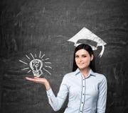 La señora presenta una bombilla como concepto de título universitario El sombrero de la graduación se dibuja sobre su cabeza Fotografía de archivo libre de regalías