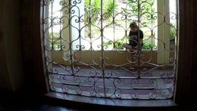 La señora que se sentaba que jugaba con el teléfono elegante fuera de la puerta del hierro de la iglesia adornó parrillas