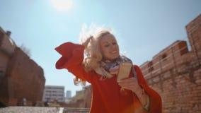 La señora rubia es sonriente y que camina y de lectura del servicio de noticias en teléfono en luz del sol almacen de video