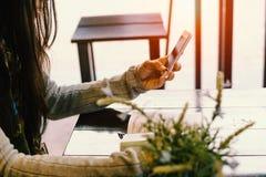 La señora se sienta y se relaja en el café, sosteniendo el teléfono disponible Imagen de archivo