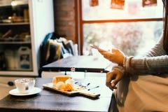La señora se sienta y se relaja en el café, sosteniendo el teléfono disponible Fotos de archivo libres de regalías