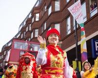 La señora se vistió en la ropa del chino tradicional que agitaba su mano Fotografía de archivo