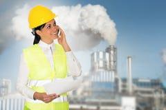 La señora sonriente dirige hablar en el teléfono y la fábrica en th Imagen de archivo libre de regalías