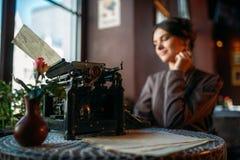 La señora sonriente se sienta por la tabla con la máquina de escribir antigua Fotos de archivo