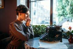 La señora sonriente se sienta por la tabla con la máquina de escribir antigua Fotos de archivo libres de regalías