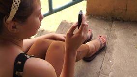 La señora utiliza el teléfono móvil para comunicar almacen de metraje de vídeo