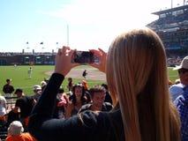 La señora utiliza Iphone para fotografiar el juego de béisbol de la muchedumbre Foto de archivo libre de regalías