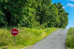 La se?al de tr?fico no entra No hay entrada a ese lado El camino entra en la dirección equivocada ?rboles verdes y cielo azul imagen de archivo libre de regalías