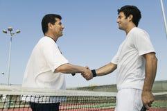 La secousse de joueurs de tennis remet le filet sur la vue de côté de cour Image stock