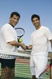 La secousse de joueurs de tennis remet le filet sur le portrait de cour Images stock