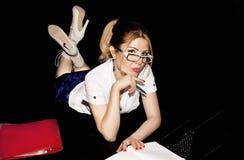 La secrétaire de fille dans le bureau pendant la pensée d'heures de travail résolvent Images stock